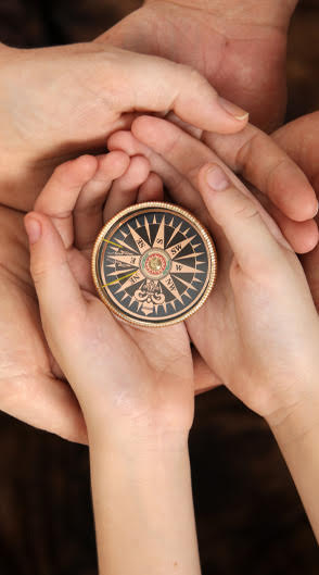 Adult's and child's hands holding a compass