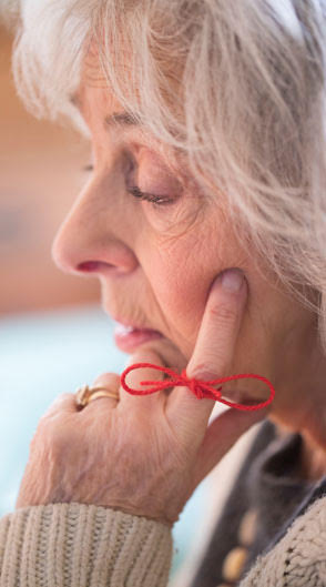 Older woman with a red string tied around her finger