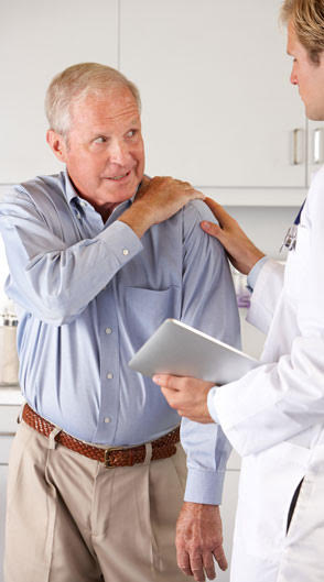 Older man holding his shoulder and looking at the doctor